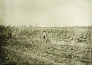 Прапорщик  Грогор Реймах-Ринн  ( в центре) стоит в воронке, образовавшейся от попадания русской бомбы во время обстрела немецкой батареи, прозванной Эльза.