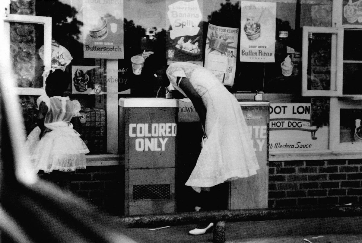 Афро-американская девушка у уличных питьевых фонтанчиков с надписями Только для белых и Только для цветных
