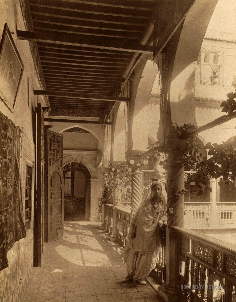 1880. Женщина в галерее с видом на внутренний двор