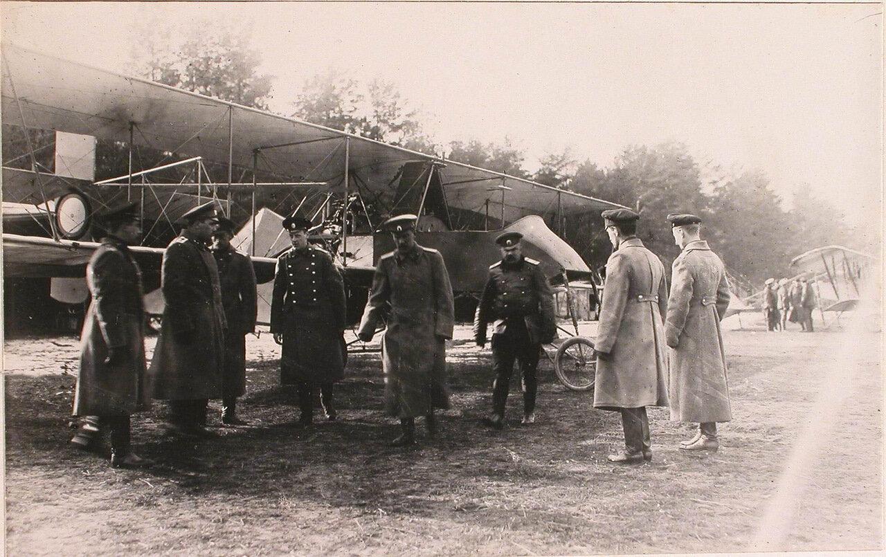 43.  Генерал Фогель (в центре) и сопровождающие его офицеры за осмотром летательных аппаратов на аэродроме во время инспектирования 5-ой армии при формировании V-го авиадивизиона