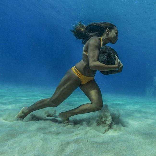 Тренировка выносливости у серфингистки. Она бегает по дну океана с 20-килограммовым камнем, для того