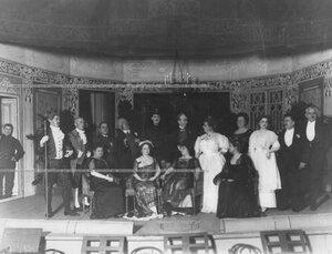 Группа участников спектакля в артистических костюмах на сцене.