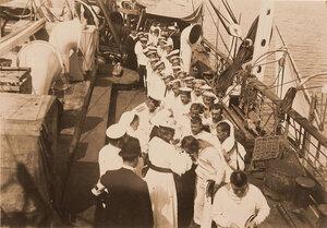 Председательница Комитета русских дам в Париже О. Д. Нелидова, раздаёт членам команды плавучего госпиталя Орел кресты, и образки, (присланные с Афонской горы).