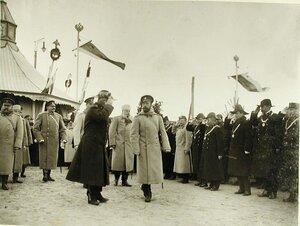 Военные и гражданские чины приветствуют императора Николая II,прибывшего на военный смотр;за императором следуют великий князь Михаил Александрович и генерал-адъютант Н.В.Клейгельс