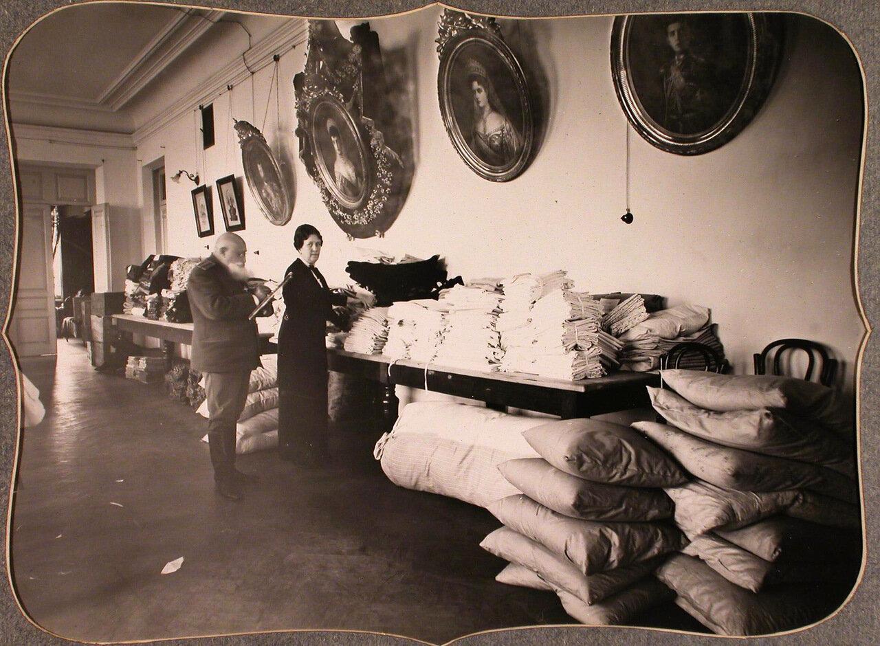 20.Служащие Красного Креста за проверкой вещей на складе, устроенном в одном из помещений общины