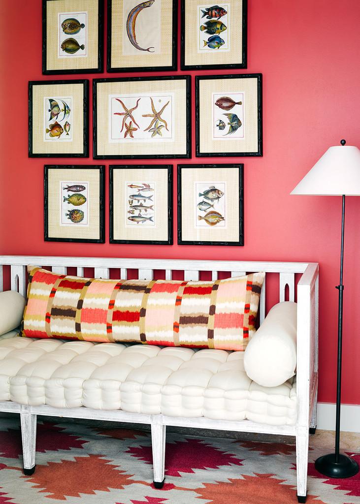 белый диван на фоне красной стены, постеры с изображением рыб и морских звезд