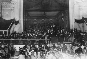 Хор, оркестр консерватории, группы учеников и преподавателей на сцене зала консерватории.