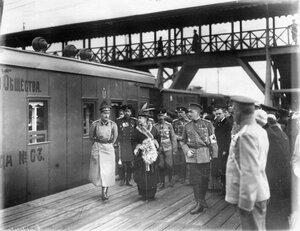 Группа военных врачей и интендантов с великой княгиней Марией Павловной и великим князем Андреем Владимировичем (1-й слева) обходят поезд по перрону вокзала
