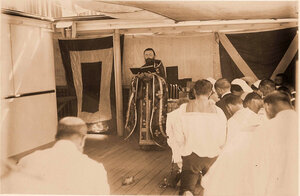 Священник и группа командиров и офицеров на палубе во время церемонии освящения плавучего госпиталя.