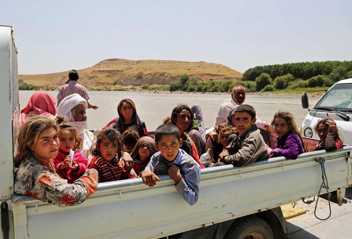 Группа беженцев в кузове малотоннажного грузового автомобиля во время движения по понтонному мосту