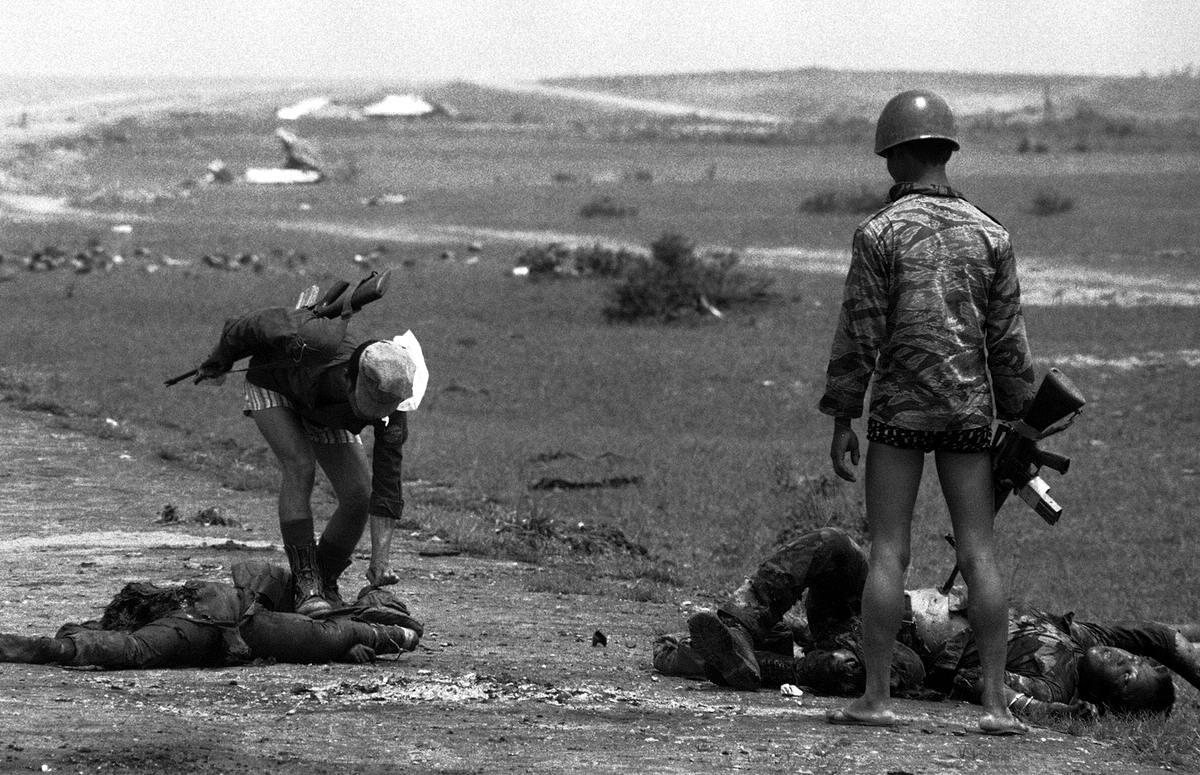 Мародерство: Южно-вьетнамские морские пехотинцы занимаются обыскиванием найденых трупов в поисках сигарет и каких-либо ценностей на оборонительной линии в 20 км севернее города Хюэ
