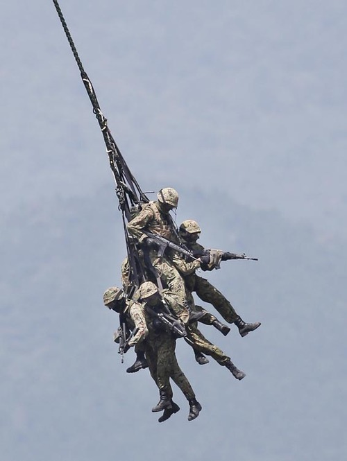 Japan Ground Self-Defense Force soldiers hang down from a helicopter during an annual live firing exercise at Higashi Fuji range in Gotemba, southwest of Tokyo, Tuesday, Aug. 20, 2013. (AP Photo/Koji Sasahara)
