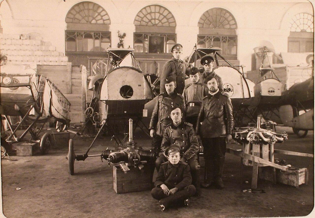 28. Группа механиков и солдат авиароты у летательного аппарата в сборочной мастерской. Псков