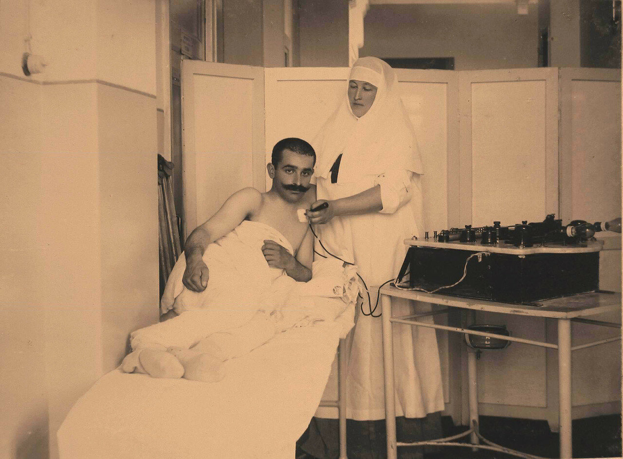 26. Сестра милосердия проводит сеанс электротерапии раненому офицеру