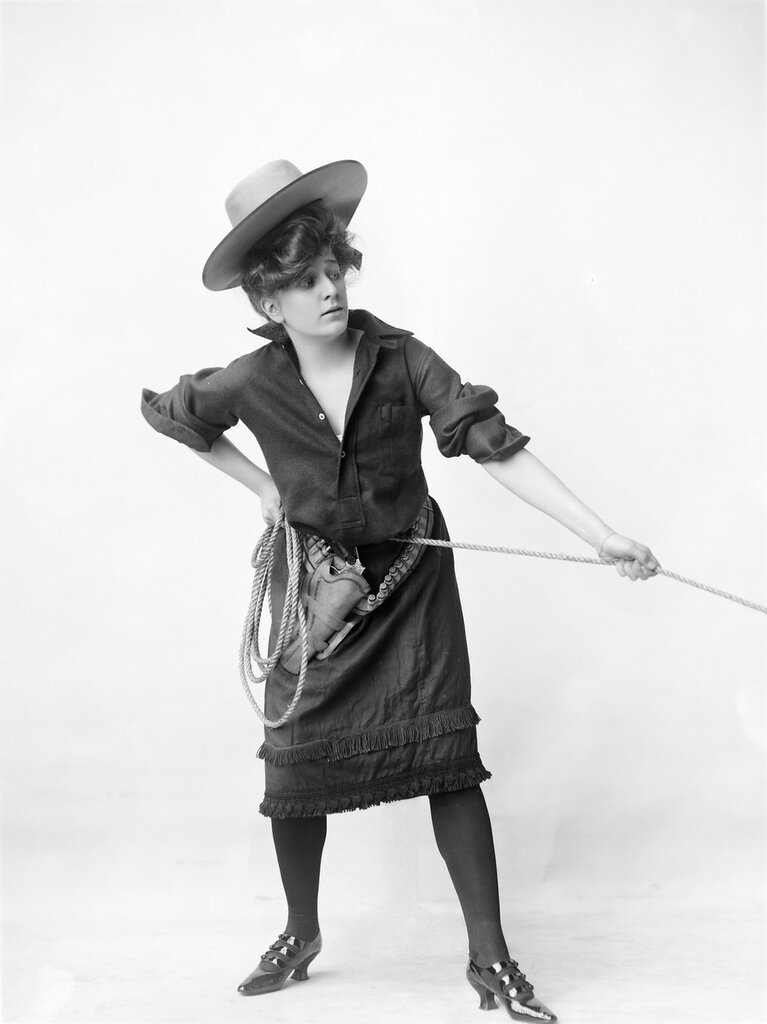 Studio portrait of a woman dressed as a cowgirl who pulls on a rope. 1903.