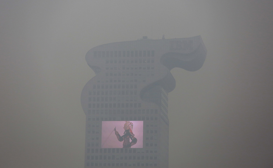 A building and a large screen seen through thick smog in Beijing on December 8, 2015, as China's