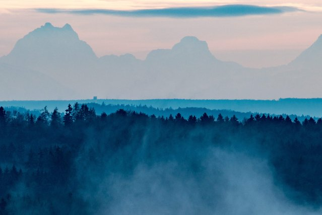 An early morning mist veils the view from the Bavarian Forest onto the Alps near the town of Lalling