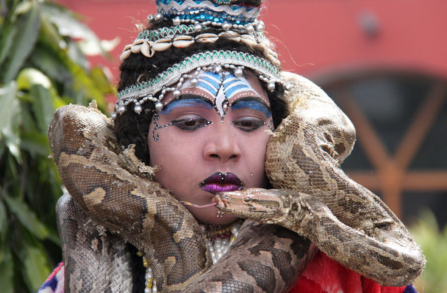 A boy dressed as Hindu Lord Shiva wraps a python around his neck before performing at a park near a