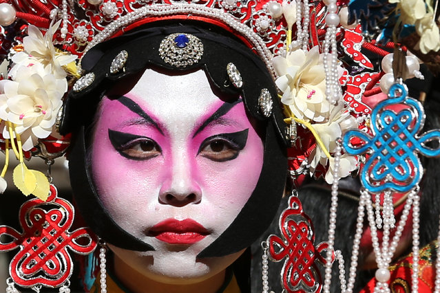 A woman dressed in traditional Chinese costumes waits to perform in celebration of the Chinese New Y