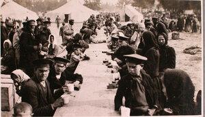 Беженцы пьют чай за столами вблизи палаток, соединительного врачебно-питательного пункта, организованного отрядом Красного Креста В.М.Пуришкевича.