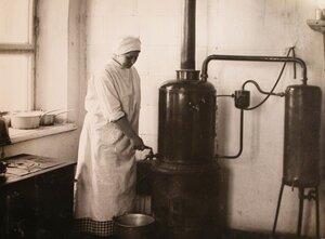 Медицинская сестра наливает кипячёную воду из титана в ведро.