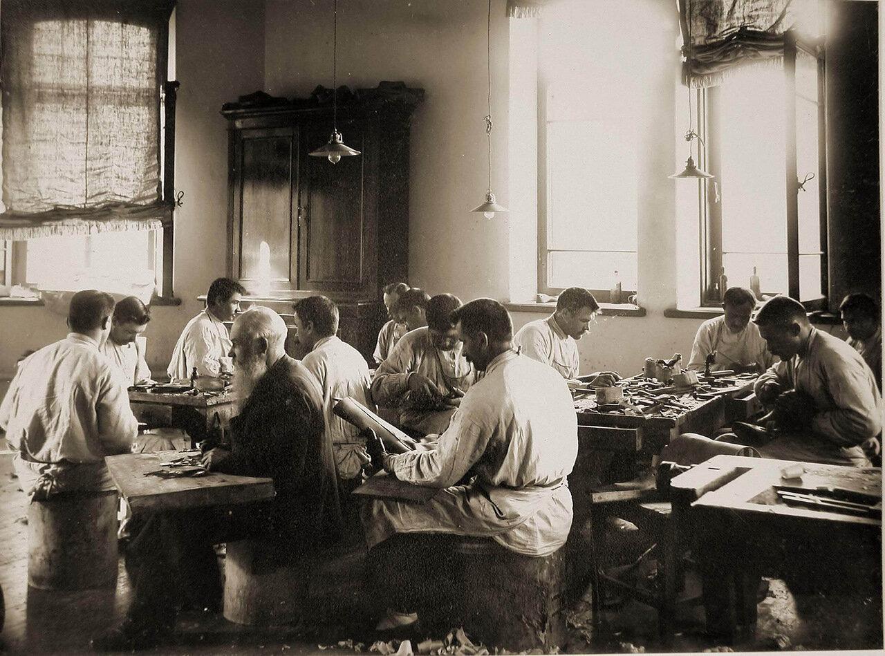 13. Группа призреваемых за работой в сапожной мастерской