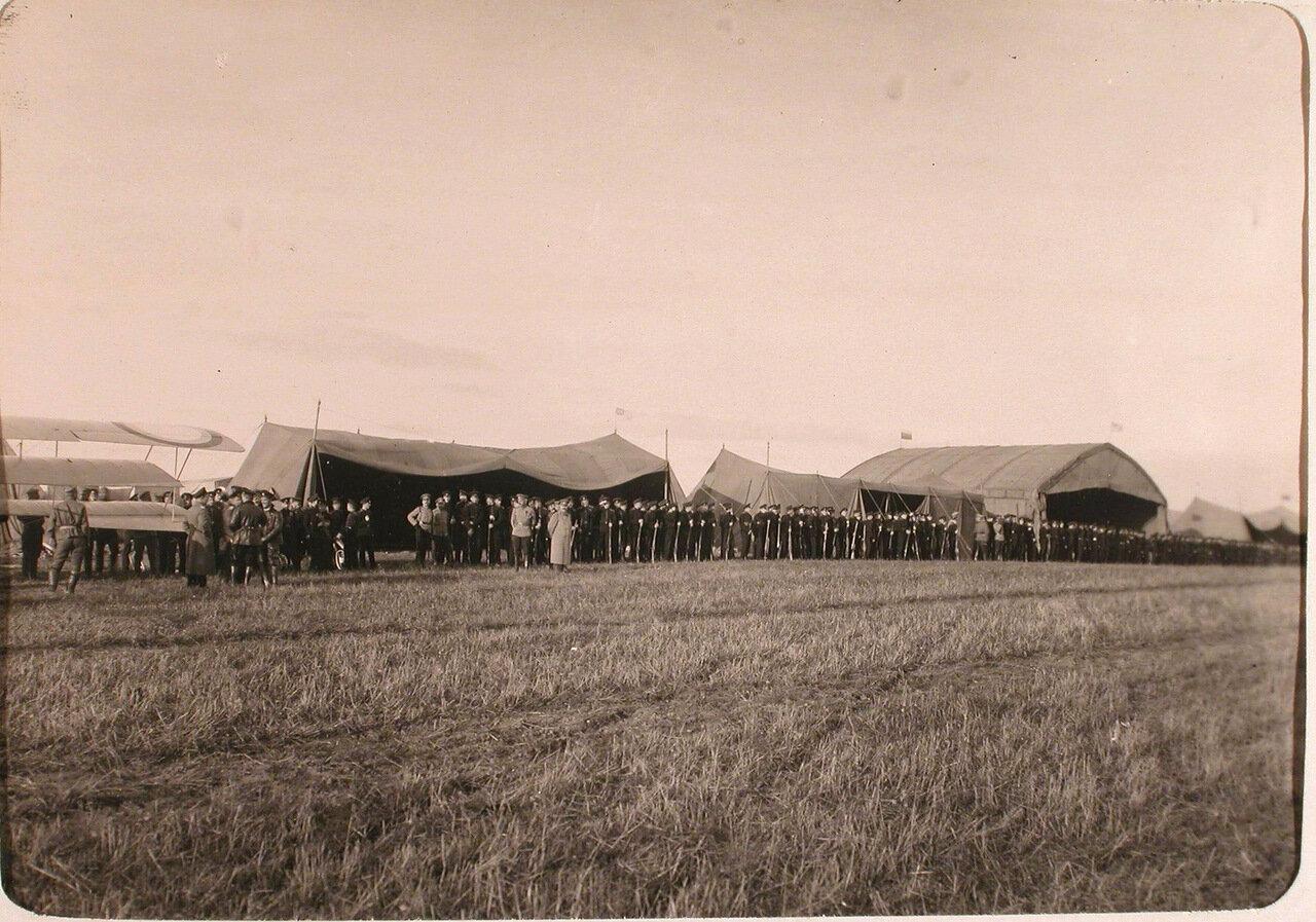 14.Группа кадетов в строю на аэродроме перед ангаром с летательными аппаратами во время посещения авиаотряда. Псков