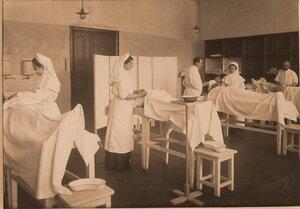 Врачи и сестры милосердия во время перевязки раненых в перевязочной на III этаже госпиталя.
