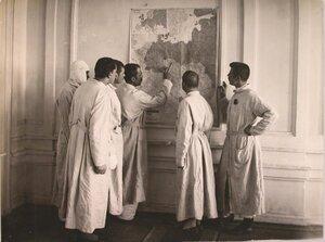 Группа раненых у карты военных действий в коридоре госпиталя.