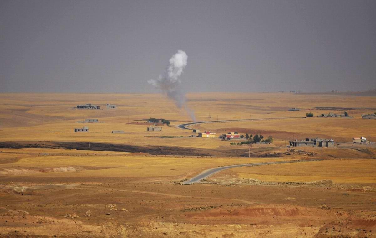 Дым, который поднимается в результате боестолкновения, возникшего между военизированными формированиями курдов и боевиками ИГИЛ к западу от иракского города Мосул