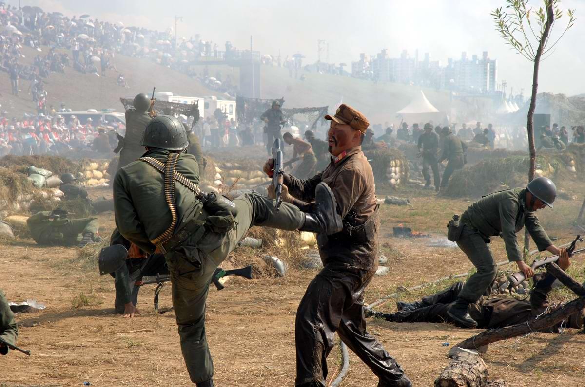 Сцены сражений между солдатами армий Северной и Южной Кореи времен военного конфликта начала 1950-х годов в исполнении переодетых солдат южнокорейской армии - 1