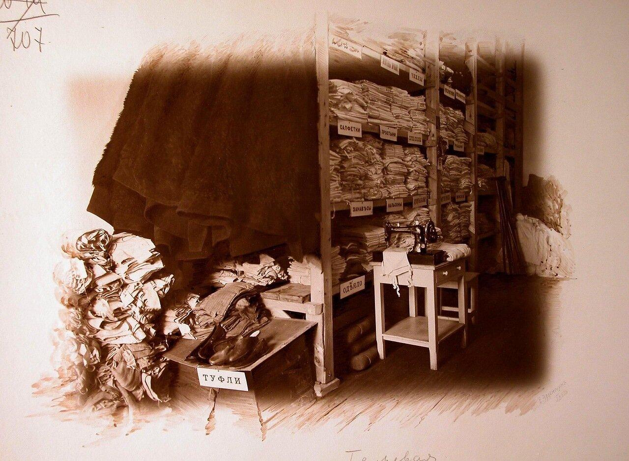 12. Вид части кладовой комнаты госпиталя; в центре на тумбочке - швейная машинка