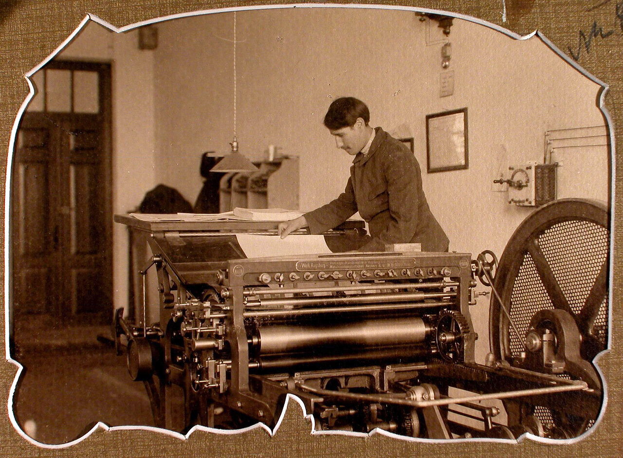 Печатник типографии за работой на печатной машине