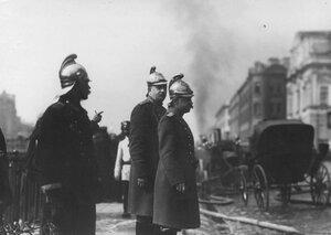 Брандмайор с помощником наблюдает за тушением пожара.