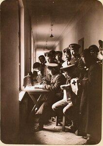 Студенты Политехнического института за шитьем повязок с Красным Крестом на ручной швейной машинке.
