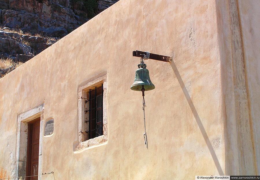 Небольшой колокол на стене здания на острове Спиналонга