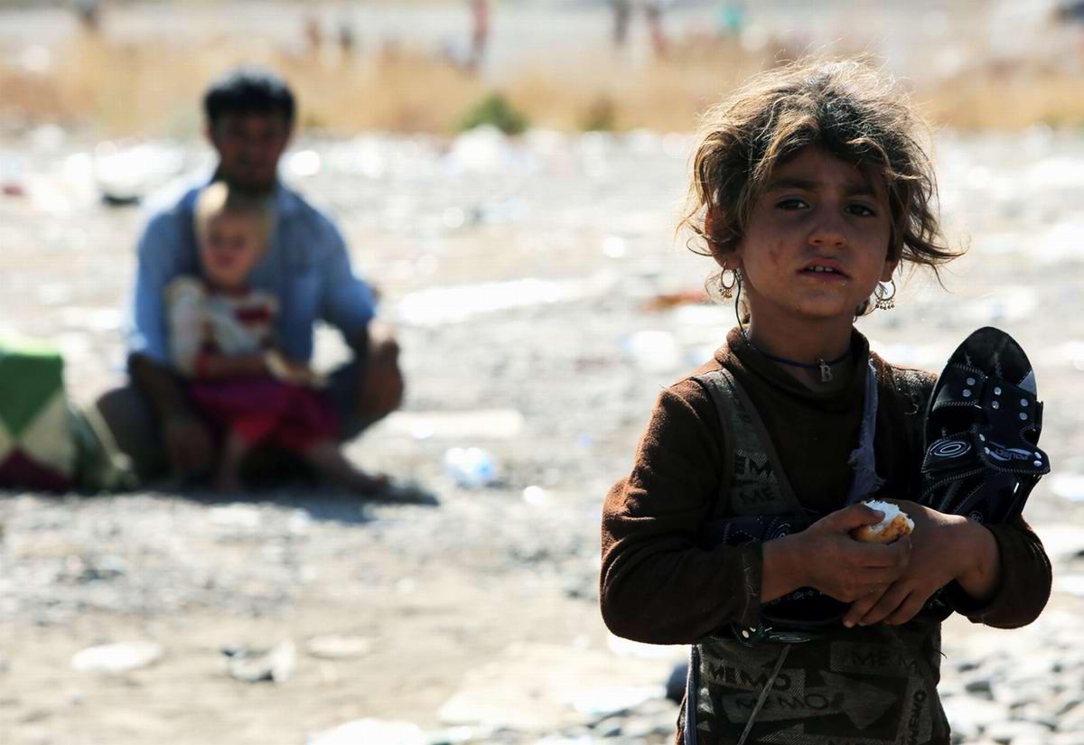 Девочка из лагеря беженцев с куском хлеба и только что полученными новыми шлепанцами