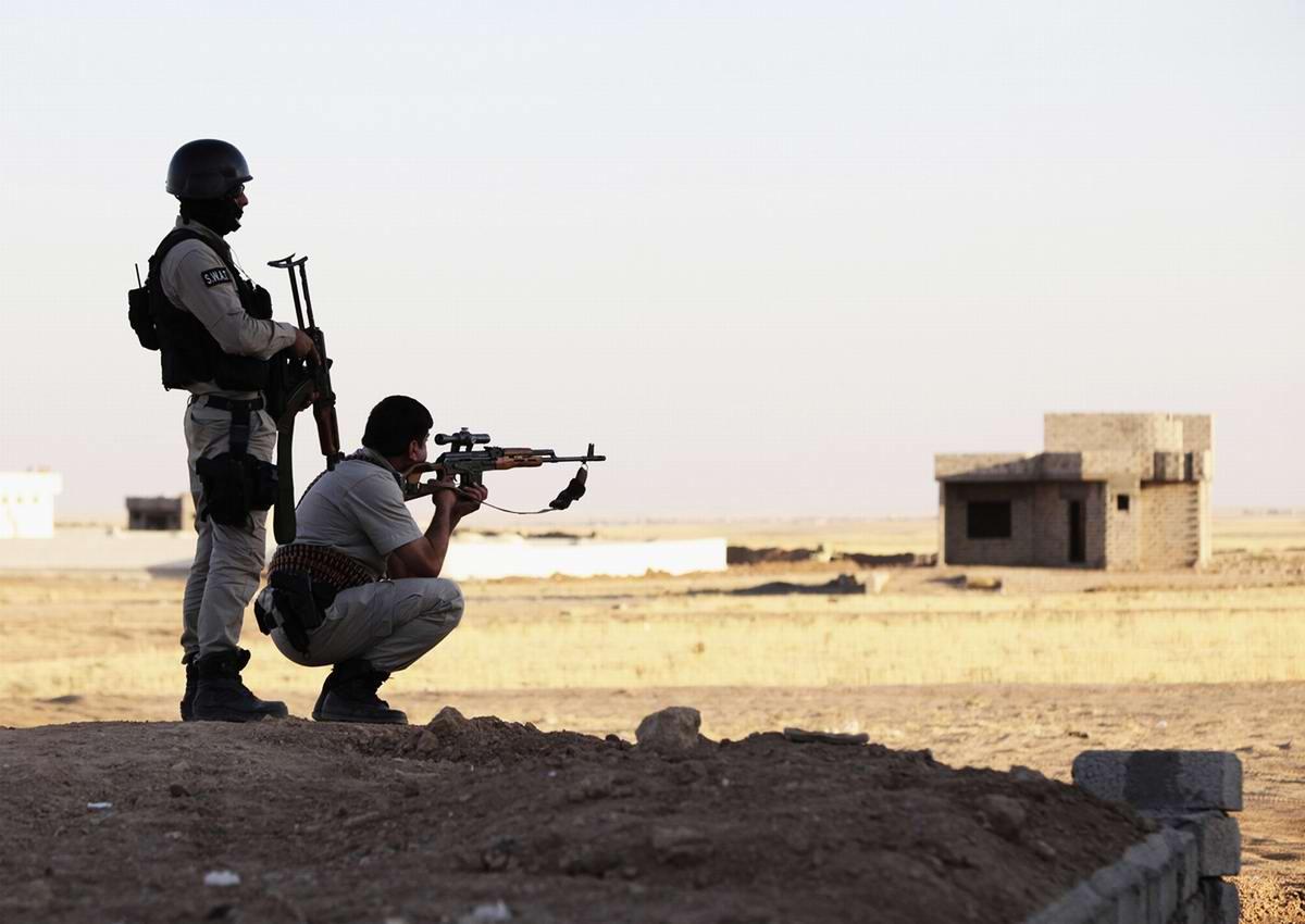 Снайперы военизированных формирований Иракского Курдистана наблюдают за окружающей обстановкой на окраине одного из селений в окрестностях города Ниневия