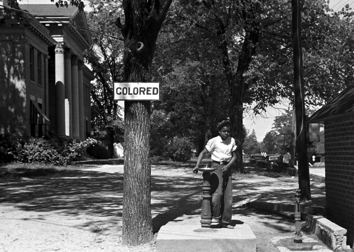 Негритянский ребенок у уличного питьевого фонтанчика с надписью Для цветных