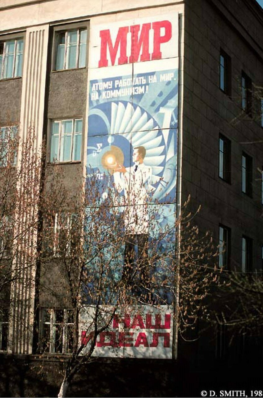 Плакат «Атом (Рэй Палмер) на службе у коммунизма» на неопознанном здании