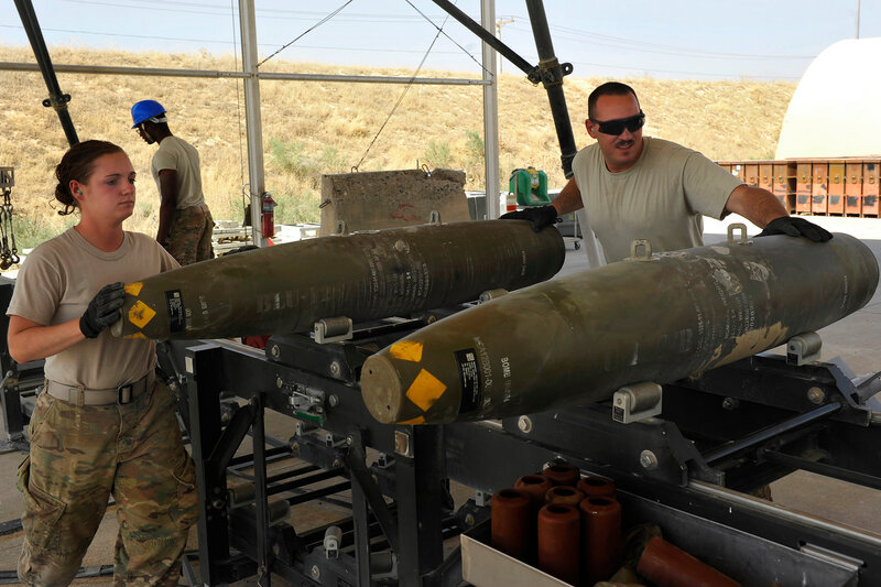 BAGRAM AIRFIELD, Afghanistan -- U.S. Air Force Airman 1st Class Casey Cain and Senior Airman Christopher Reed slide a GBU-38 on a conveyor during a bomb build here on Aug. 14, 2014. Cain is a reservist from the 442nd Fighter Wing, Whiteman AFB, Mo. and a