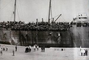Пароход с эвакуируемыми нижними чинами и запасными с Дальнего Востока, причаливший к берегу, в городском порту.