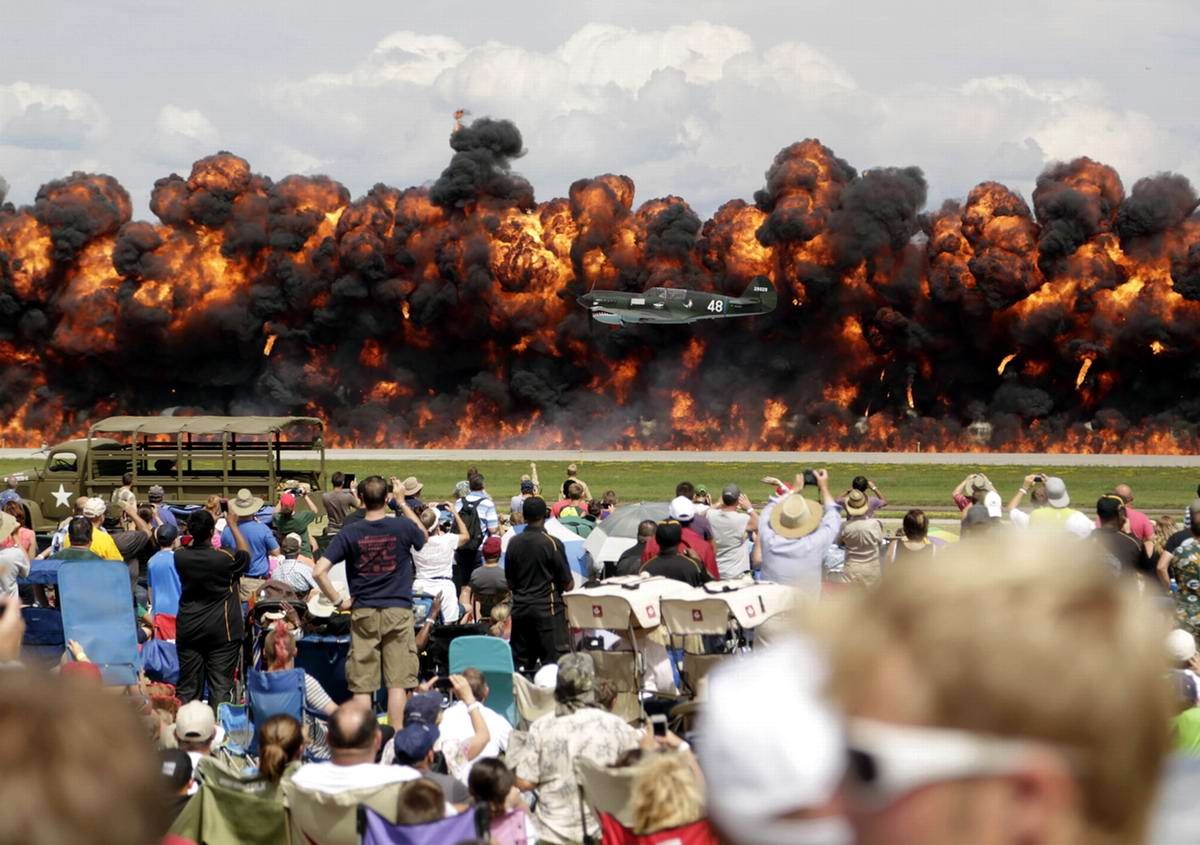 Американский самолет времен Второй мировой войны летит перед стеной огня в процессе инсценировки японского нападения на Перл-Харбор во время авиашоу на территории штат Висконсин (США)