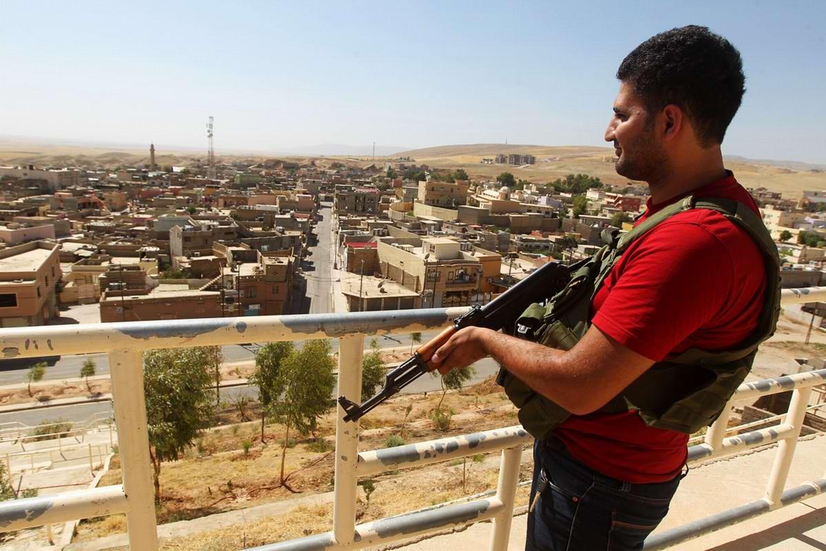 Курдский боец на наблюдательной площадке на крыше дома (окраина города Дахук)