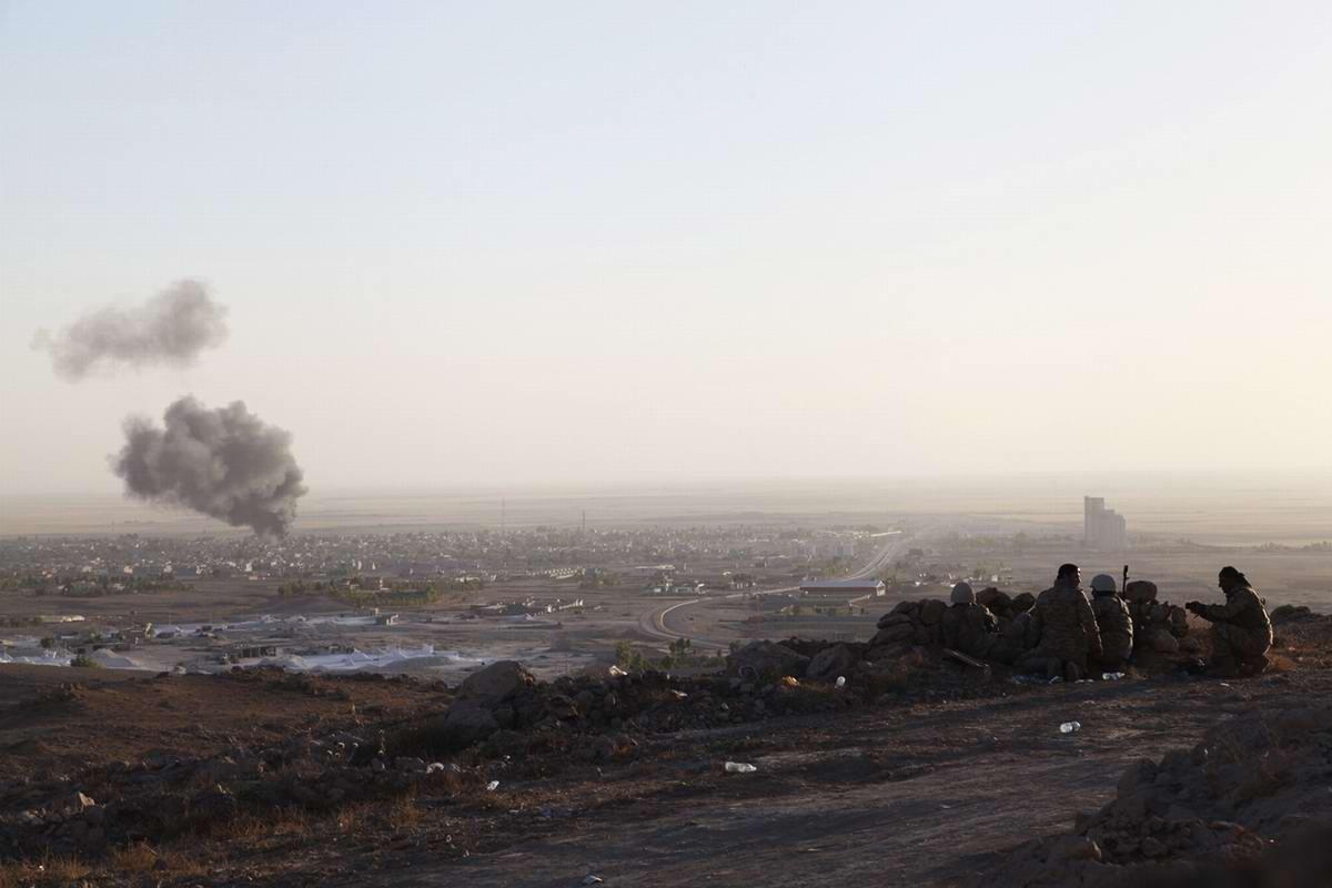 Группа бойцов военизированных формирований Иракского Курдистана на позиции возле города Махмур наблюдают за дымом пожарищ, которые возникли в результате столкновений с боевиками ИГИЛ