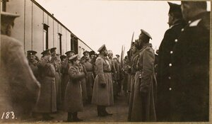 Император Николай II (в центре), приехавший с наследником цесаревичем Алексеем Николаевичем (стоит за императором) для осмотра Рижского укрепленного района, на платформе перед строем ординарцев во время церемонии их