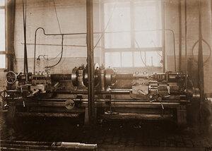 Вид токарного станка с зажатой в нем деталью в одном из цехов мастерской.