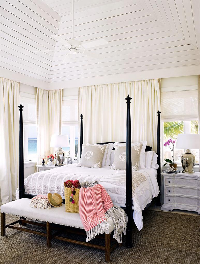 спальня в доме на побережье, кровать со столбиками, белые стены, белый интерьер, плетеный ковер, белые шторы