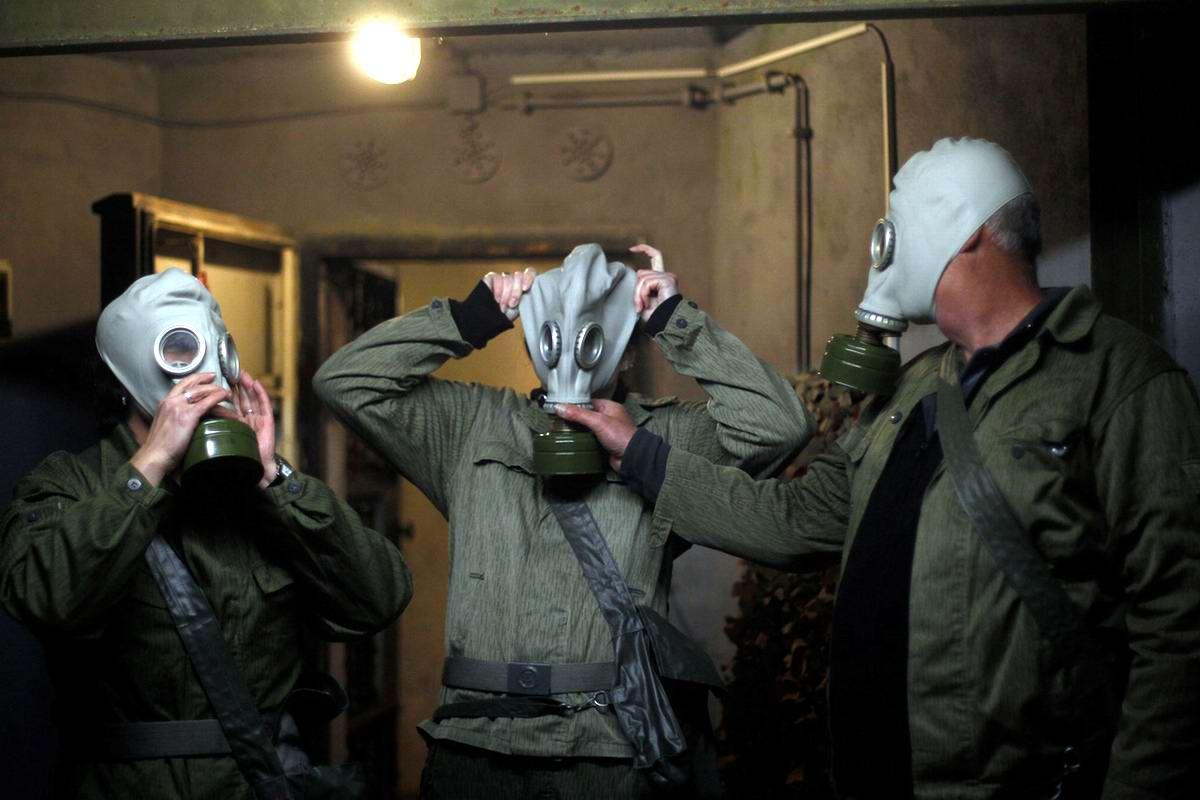 Гости одевают на себя военные противогазы