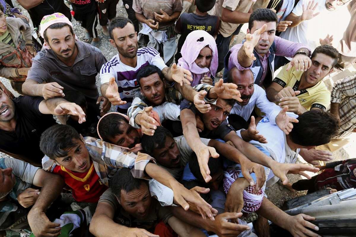 Беженцы, тянущие свои руки за гуманитарной помощью